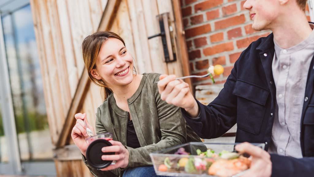 Zwei-junge-Menschen-nutzen-ORNAMIN-Food-to-go-Mehrweggeschirr-zum-essen-unterwegs